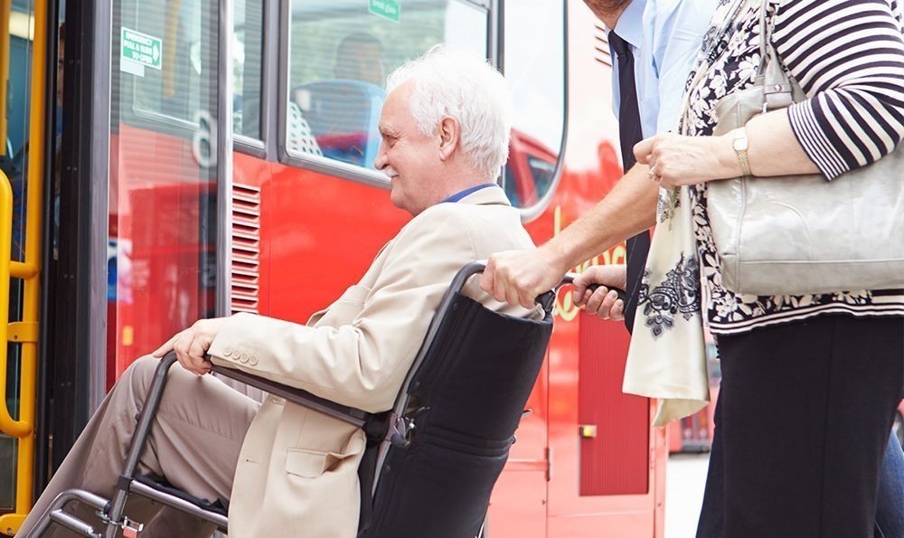 Elderly gentleman being helped onto a bus in a wheelchair